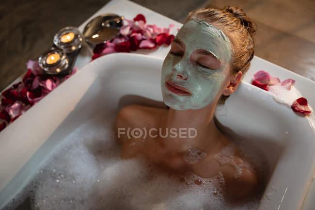 Close up vista frontal de uma jovem mulher caucasiana deitada em um banho com uma máscara facial, com pétalas e velas acesas ao redor da banheira . — Fotografia de Stock