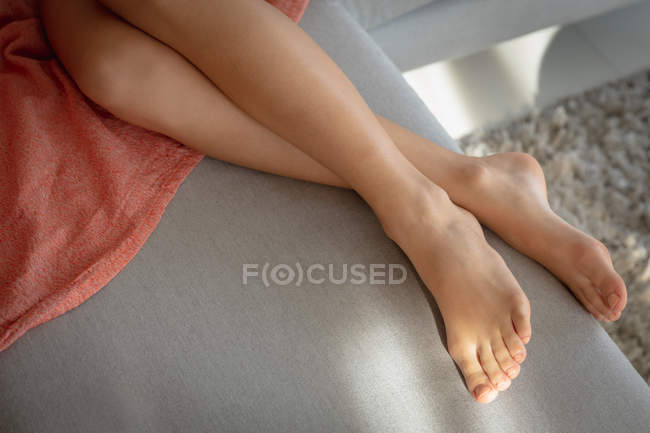Close up of the legs of woman lying on a sofa. — стокове фото