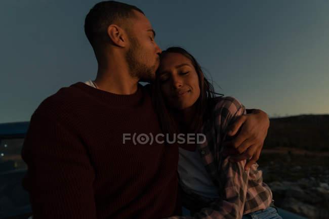 Close up vista frontal de um jovem casal misto sentado do lado de fora beijando e abraçando ao entardecer durante uma parada em uma viagem de carro . — Fotografia de Stock