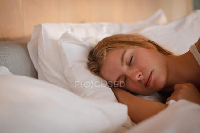 Крупним планом молода кавказька жінка спить в ліжку. — стокове фото