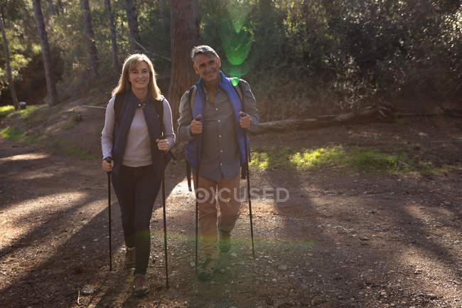 Vista frontale di una donna e un uomo caucasici maturi che indossano zaini e utilizzano bastoni da nordic walking che camminano su un sentiero attraverso una foresta durante un'escursione, retro illuminato dalla luce del sole — Foto stock