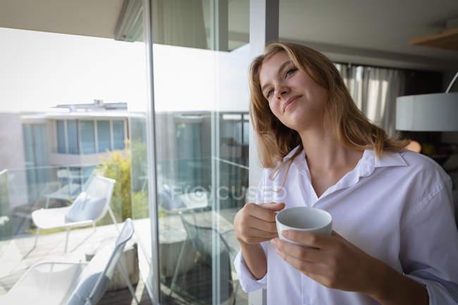 Вид спереди на молодую кавказку в белой рубашке с чашкой кофе и улыбкой . — стоковое фото