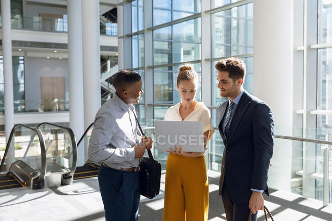 Front view of young Caucasian businesswoman standing between a young African American and a young Caucasian businessmen looking at a laptop in a modern office lobby. — Stock Photo