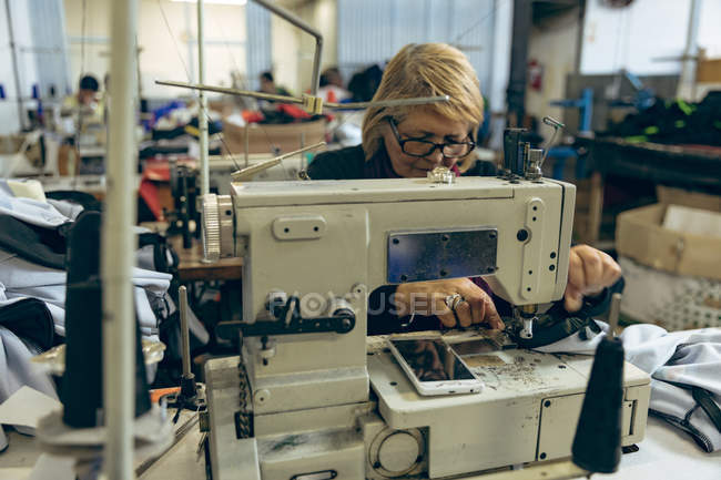 Front view close up of a middle aged Caucasian woman sitting and operating a sewing machine at a sports clothing factory. — Stock Photo
