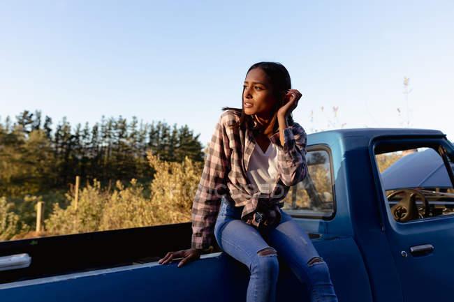 Vue de face d'une jeune femme métisse assise à l'arrière d'une camionnette regardant ailleurs, lors d'un arrêt sur une route . — Photo de stock