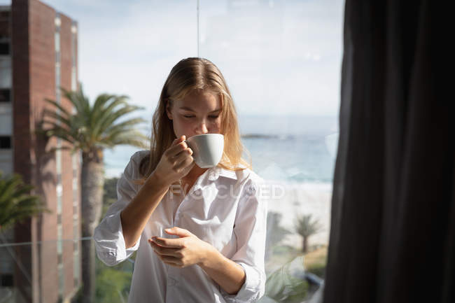Front view close up of a young Caucasian woman wearing a white shirt standing on a balcony drinking a cup of coffee and looking down, palm trees and beach in the background. — Stock Photo