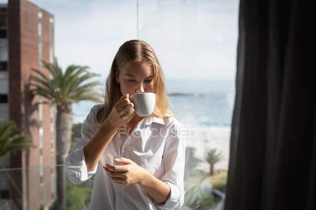Vista frontale da vicino di una giovane donna caucasica che indossa una camicia bianca in piedi su un balcone bevendo una tazza di caffè e guardando in basso, palme e spiaggia sullo sfondo . — Foto stock