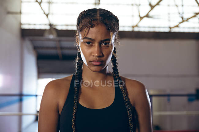 African american female boxer looking at camera in boxing club. Strong female fighter in boxing gym training hard. — стокове фото