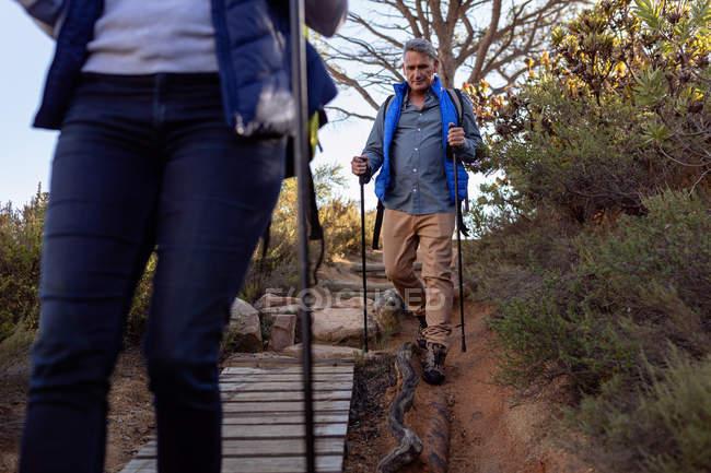 Vue de face gros plan d'un homme et d'une femme caucasiens matures portant des sacs à dos et utilisant des bâtons de marche nordique marchant en descente sur un sentier lors d'une randonnée . — Photo de stock