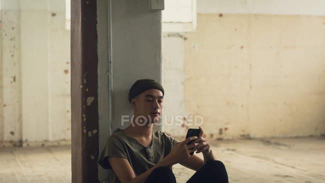 Opinião lateral um homem latino-americano novo com as perfurações que desgastam uma camisa cinzenta escura e um Beanie que sentam-se ao usar um telefone móvel dentro de um armazém vazio — Fotografia de Stock
