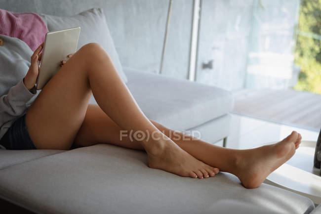 Gros plan des jambes d'une femme allongée sur un canapé à l'aide d'une tablette . — Photo de stock