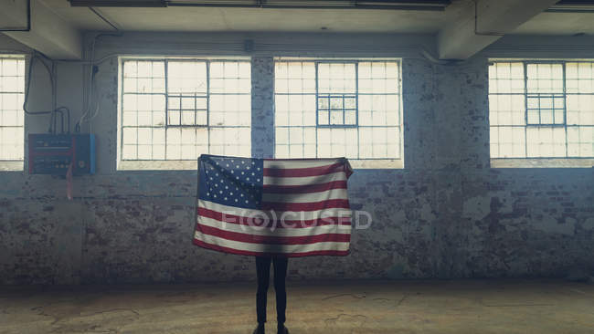 Silhouette of a man holding out an American flag inside an empty warehouse — Stock Photo