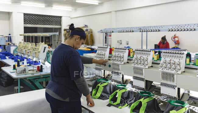 Вид сбоку молодой смешанной расы женщины, управляющей автоматизированной швейной машиной, сшивающей рубашки на фабрике спортивной одежды, на заднем плане другие коллеги также работают с машинами . — стоковое фото