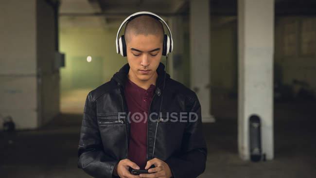 Vista frontale di un giovane ispano-americano che indossa una giacca di pelle nera sopra una camicia marrone e cuffie mentre utilizza un telefono cellulare all'interno di un magazzino vuoto — Foto stock
