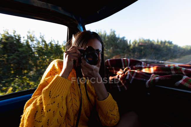 Close up of a young mixed race woman sitting in the front passenger seat of a pick-up truck taking photos with a camera during a road trip — Stock Photo