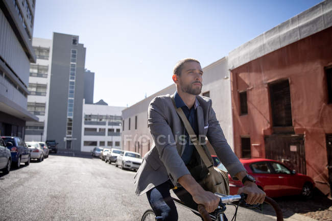 Front view close up of a young Caucasian man riding his bicycle in a city street. Digital Nomad on the go. — стокове фото