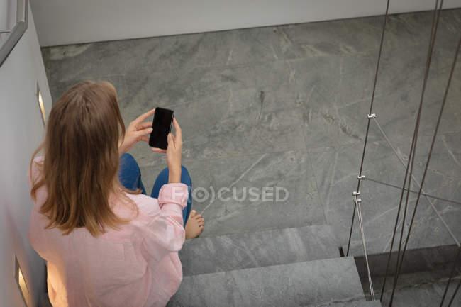 Высокий вид сзади молодой белой женщины в розовой рубашке, сидящей на лестнице с помощью смартфона . — стоковое фото