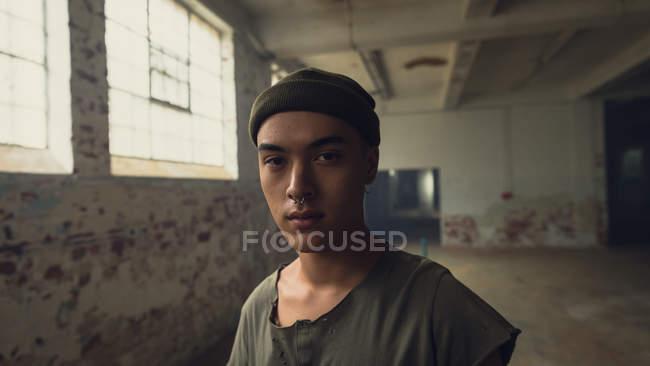 Opinião dianteira um homem latino-americano novo com as perfurações que desgastam uma camisa cinzenta escura e um Beanie que sentam-se olhando atenta à câmera ao estar dentro de um armazém vazio — Fotografia de Stock