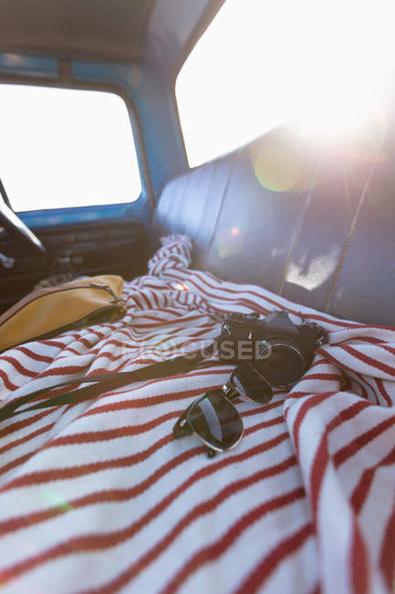 Close up of sunglasses and camera on the seat of a pick-up truck during a road trip, back lit by sunlight — Stock Photo