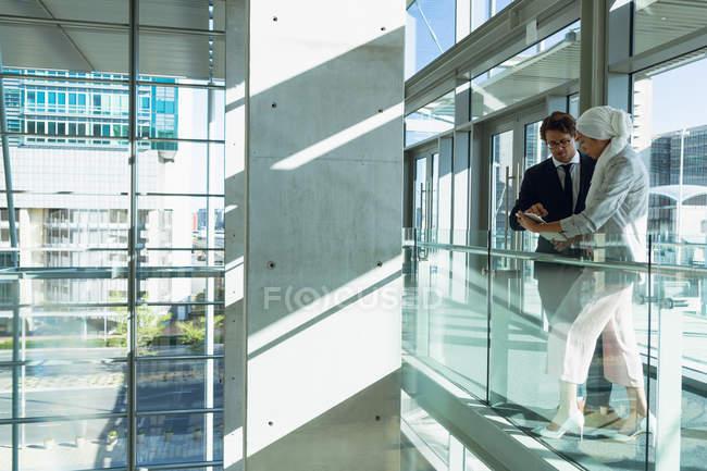 Vista laterale di uomini d'affari che lavorano insieme su tablet digitale in corridoio presso l'ufficio moderno . — Foto stock