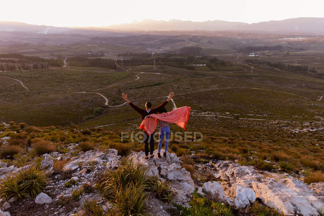 Back view of a young mixed race couple standing on a rock with a blanket over their shoulders, with their arms in the air, embracing and enjoying the view during a stop off on a road trip. — Stock Photo