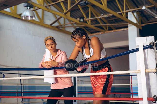 Trainer und Boxerin im Boxring im Fitnesscenter. Starke Kämpferin im Box-Fitness-Training hart. — Stockfoto
