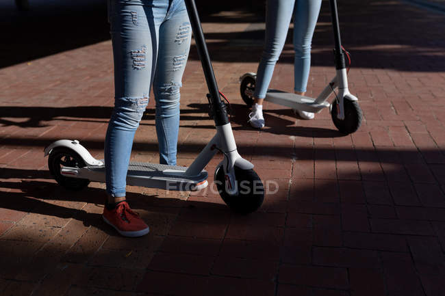 Front view low section of sisters standing with electric scooters in an urban park — Stock Photo