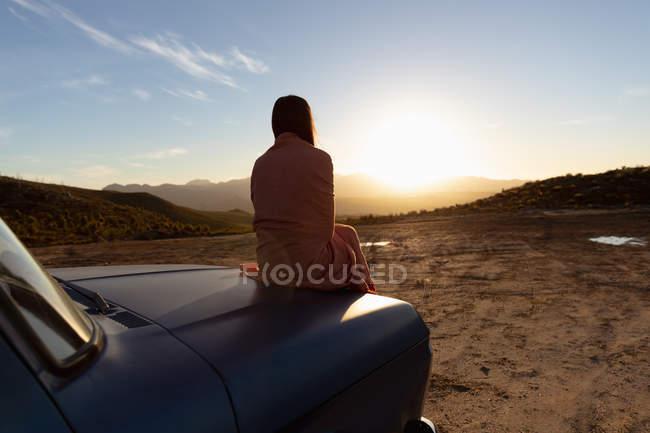 Назад вид молода жінка, сидячи на капоті пікап вантажівка насолоджуючись зору на sundown під час зупинки на дорозі поїздки — стокове фото