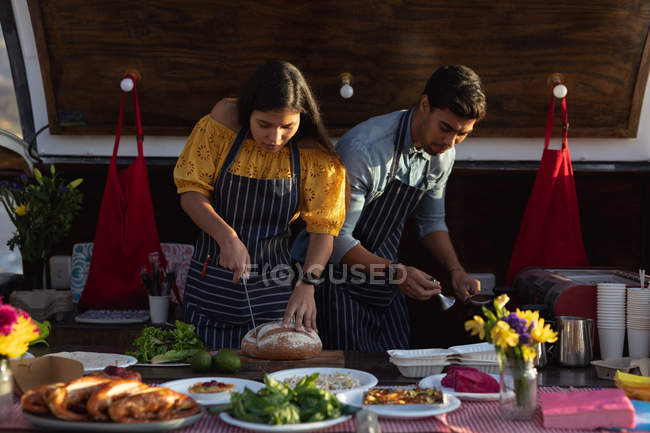 Front view close up of a young mixed race couple busy preparing food standing in an open top van offering a range of takeaway food for sale — Stock Photo