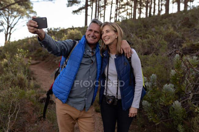 Vista frontal de perto de uma mulher branca madura e um homem usando mochilas e uma câmera, sorrindo e tirando uma selfie com um smartphone durante uma caminhada — Fotografia de Stock
