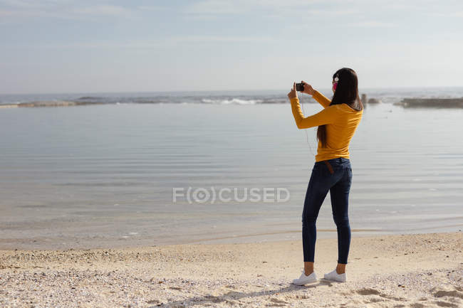 Rear view of a young mixed race woman wearing headphones standing on a beach taking photos of the sea with her smartphone — Stock Photo