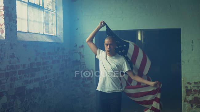 Вид спереди на молодого латиноамериканца в простой белой рубашке с американским флагом внутри пустого склада — стоковое фото