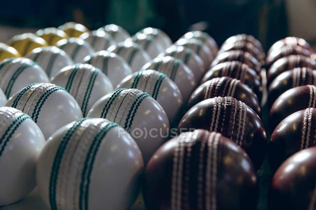 Крупним планом червоний, білий і жовтий крикет кулі в ряди в кінці виробничої лінії на заводі. — стокове фото