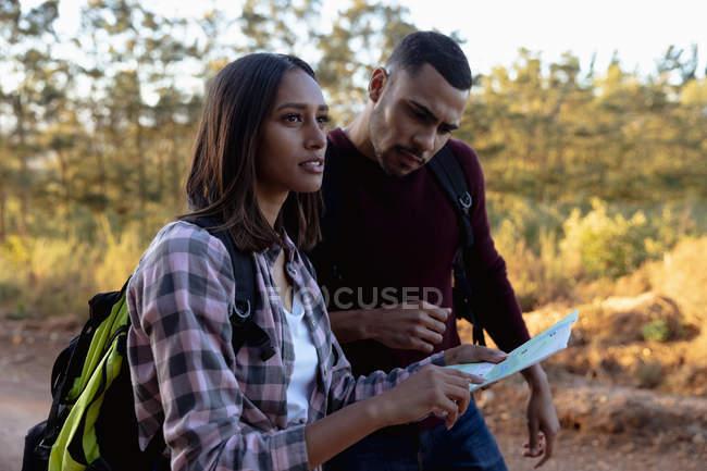 Vista laterale ravvicinata di una giovane coppia mista che indossa zaini in piedi in un ambiente rurale leggendo una mappa durante un'escursione — Foto stock