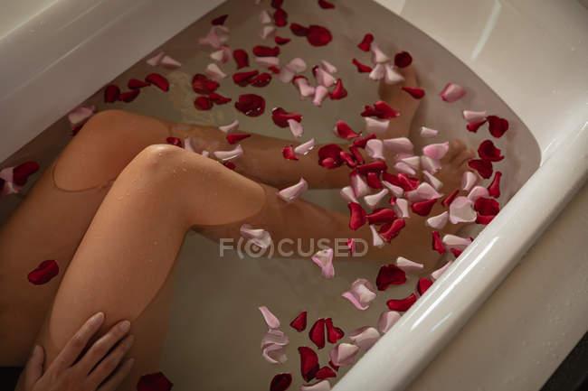 Close up vista elevada das pernas da mulher relaxando em um banho com pétalas de rosa . — Fotografia de Stock
