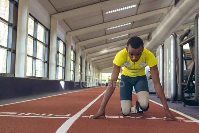 Вид спереди инвалида афроамериканского спортсмена на стартовой площадке на беговой дорожке в фитнес-центре — стоковое фото
