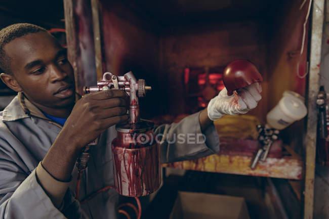 Vista lateral de cerca de un joven afroamericano de pie en un área de pintura sosteniendo una parte exterior en forma de bola de cricket de cuero rojo y rociándola con una pistola de pulverización en un taller en una fábrica de bolas de cricket . - foto de stock