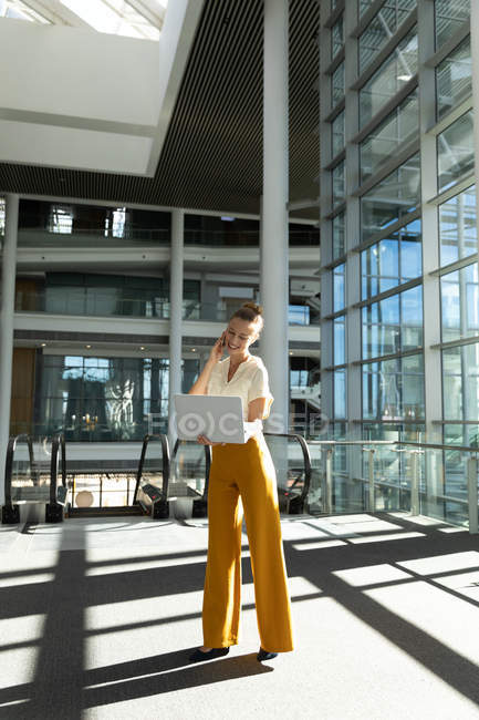 Front view view of young Caucasian businesswoman holding laptop computer and talking on phone. She is standing in front of escalators in the glass walled lobby of a modern business building and looking down. — Stock Photo
