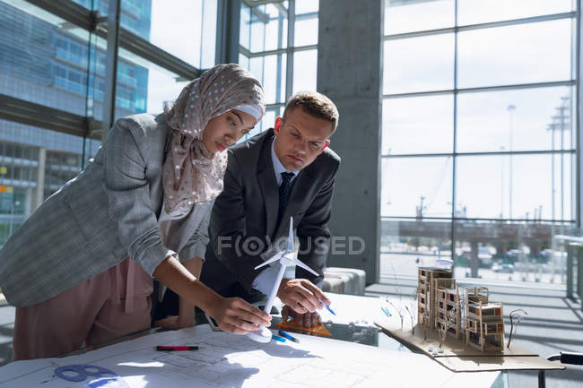 Multi-ethnic male and female architects discussing over blueprint in office. — Stock Photo
