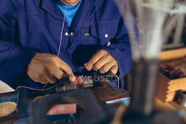Visão frontal meio homem seção de pé em uma bancada segurando fio em sua boca e mãos, costurando uma bola em uma oficina em uma fábrica de fazer bolas de críquete . — Fotografia de Stock