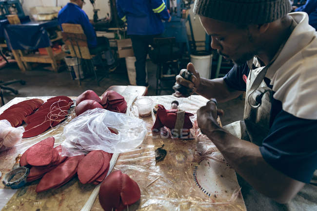 Side view close up of a young African American man wearing a hat sitting at a workbench working with cut out red leather shapes in a workshop at a factory making cricket balls — Stock Photo