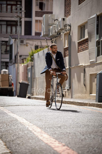 Front view of a smiling young Caucasian man carrying riding his bicycle in a city street. Digital Nomad on the go. — Stock Photo