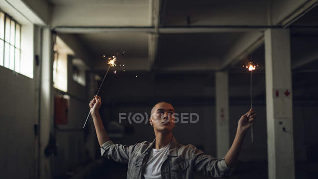 Front view of a young Hispanic-American man wearing a grey jacket over a white shirt looking away from the camera while holding lighted sparkles on both hands inside an empty warehouse — Stock Photo