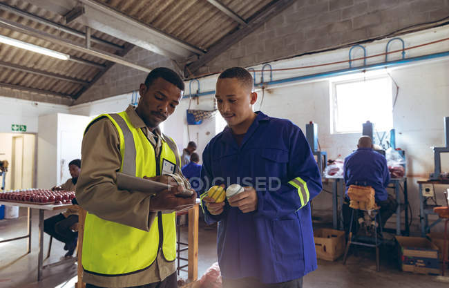 Front view of a young African American male manager holding a tablet computer and talking with a young mixed race male worker in the workshop at a cricket ball factory. — Stock Photo