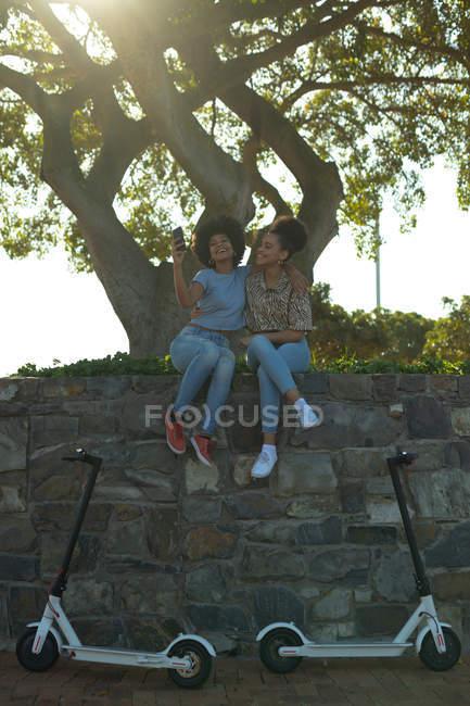 Frontansicht von zwei jungen lächelnden erwachsenen gemischten Rennschwestern, die an einer Wand in einem Stadtpark sitzen, ein Smartphone benutzen und Selfies machen, ihre Elektroroller unter ihnen geparkt, hinterleuchtet — Stockfoto