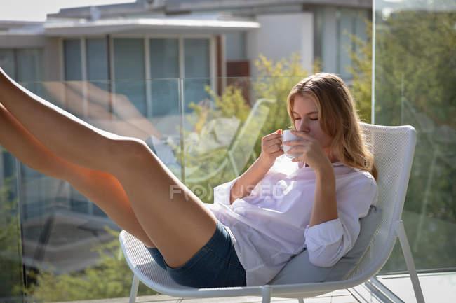 Vue de face gros plan d'une jeune femme caucasienne portant une chemise blanche assise sur une chaise sur un balcon buvant du café au soleil les jambes en l'air, des bâtiments en arrière-plan . — Photo de stock