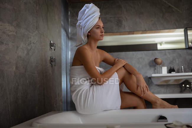 Side view of a young Caucasian woman sitting on the edge of a bath, wearing a bath towel with her hair wrapped in a towel, in modern bathroom. — стокове фото
