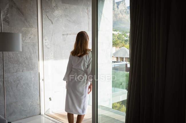 Visão traseira de uma jovem caucasiana vestindo um roupão de banho apoiado em uma porta da varanda com vista para fora . — Fotografia de Stock