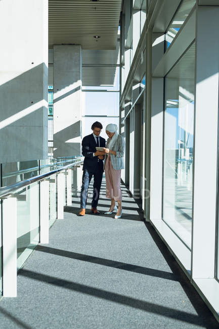 Фронтальный вид деловых людей, работающих вместе на цифровом планшете в современном офисе . — стоковое фото