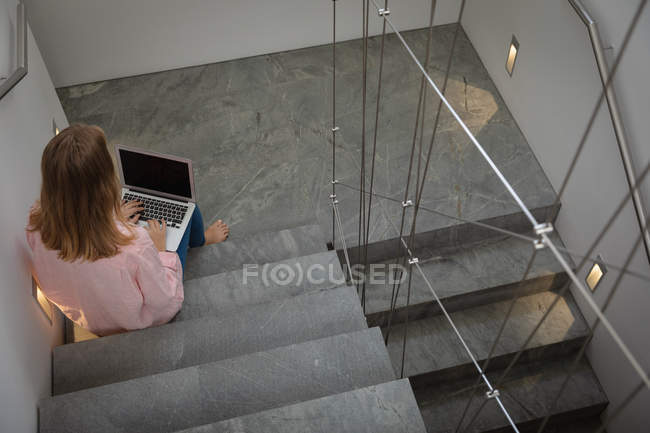 Elevated rear view of a young Caucasian woman wearing a pink shirt, sitting on a staircase using a laptop computer. — стокове фото